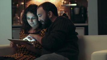 casal usando tablet no sofá à noite no quarto
