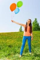 Smiling girl holding three balloons in summer