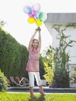 Young Girl Holding Up Balloons In Lawn