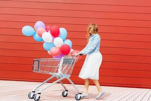 girl rolling shopping cart with balloons photo