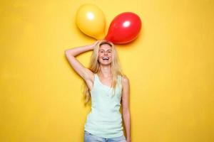 Funny young woman laughing with balloons photo