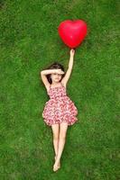 hermosa niña tendida en el césped y sosteniendo una bola roja