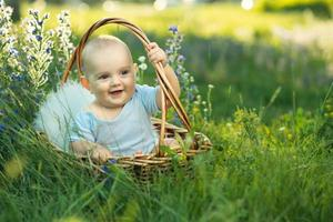 small smiling child in sliders sitting a basket