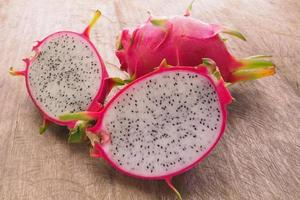 Dragon Fruit and some slice on old Wooden Table