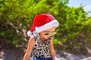 Little girl in red Santa hat on white beach outdoors