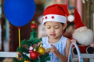 Cute little girl with santa hat present have christmas. photo
