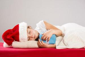 Small girl in santa hat with christmas gift photo