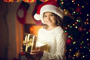 portrait of girl in Santa cap posing with glowing gift