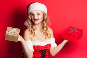 beautiful young woman wearing Santa Claus costume holding colorf photo