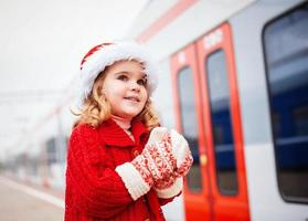 Little girl Santa waiting for a train