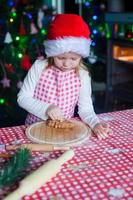 Adorable girl eating the dough for ginger cookies in kitchen