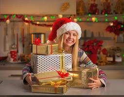 Happy teenage girl in santa hat with stack of gifts photo