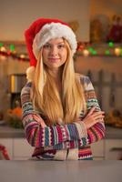 Portrait of happy teenage girl in santa hat photo