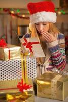 Teenager with stack of christmas present boxes reading postcard photo