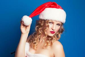 beautiful young woman wearing Santa Claus costume against blue b