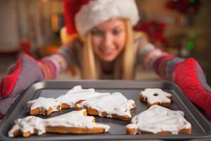 Girl in santa hat pulling out pan of cookies. Closeup photo