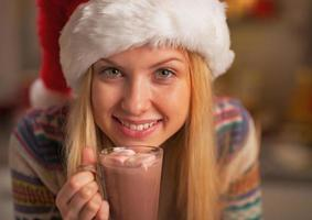 Happy teenage girl in santa hat with cup of chocolate photo