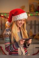 Smiling teenage girl in santa hat writing sms photo