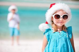 Little girl on beach wearing sunglasses and Santa hat
