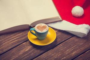 Cup of coffee with heart shape, book and christmas hat