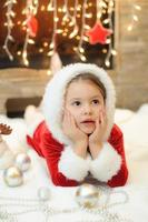Little girl dressed as Santa by the fireplace photo