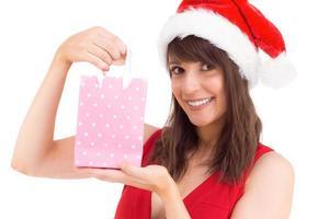 morena festiva sosteniendo una bolsa de regalo foto