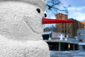 Snowman with a red nose in the city