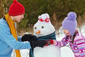 Father and daughter with snowman photo