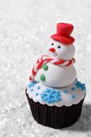 Cupcake Christmas snowman on white snow. vertical