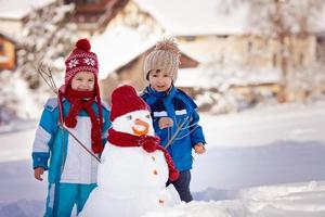 Happy beautiful children, brothers, building snowman in garden