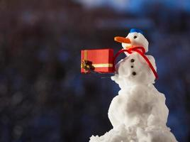 Little happy snowman with christmas gift box outdoor. Winter season.