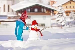 Happy beautiful child building snowman in garden, winter