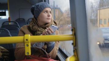donna con smartphone in sella a un autobus
