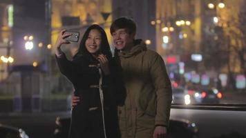 Happy teenagers smiling at smartphone camera, taking selfie, having fun together video