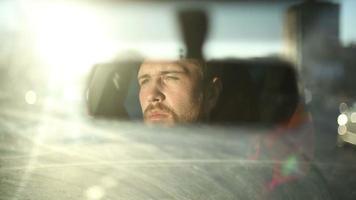 reflexo do rosto masculino no espelho retrovisor do carro