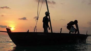 Zwei Fischer schöpften am Ende eines harten Tages bei Sonnenuntergang im Indischen Ozean Wasser aus einem alten Holzboot. Zeitlupe. video