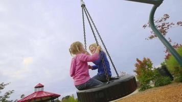 Sisters enjoy a tire swing together