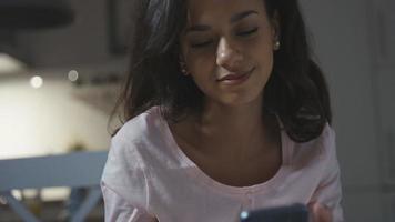 jeune femme afro-américaine assise à la table de la cuisine à la maison et en tapant sur son téléphone portable.