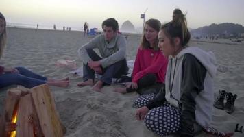 adolescentes sentam perto do fogo juntos video