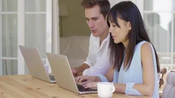 pareja trabajando juntos en computadoras portátiles