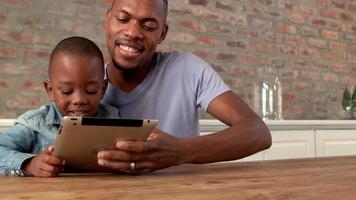 Father and son using tablet together video