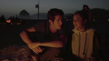 casal fofo sentado junto ao fogo