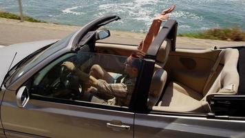 casal dirigindo conversível junto na praia