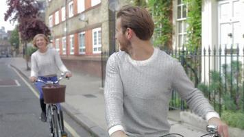 casal andando de bicicleta pela rua urbana juntos