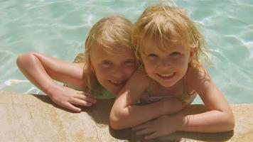 Cute sisters smile together in pool