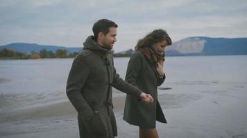 casal romântico correndo e pulando juntos à beira-mar. pessoas felizes estão de mãos dadas. jovem de casaco preto e lenço marrom está rindo e correndo juntas