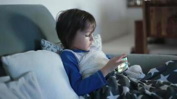 Little preschool child, boy, playing on mobile phone on the sofa at night