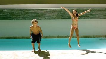 hermanos saltando juntos en la piscina