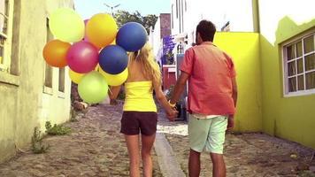 coppia che cammina insieme in un vicolo con palloncini