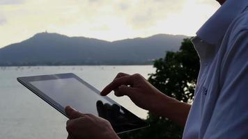 homem usando computador tablet ao ar livre.